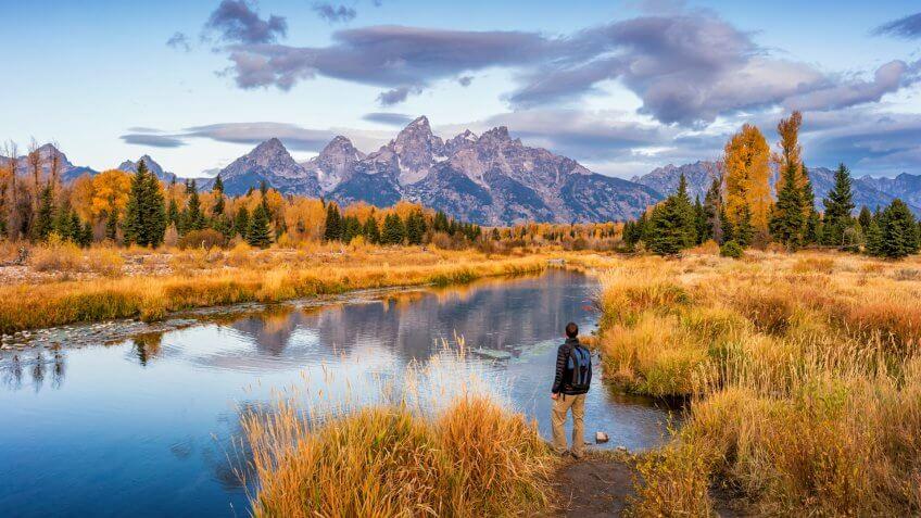 Stock photograph of hiker looking at view at Schwabacher Landing in Grand Teton National Park, Wyoming, USA, at dawn.