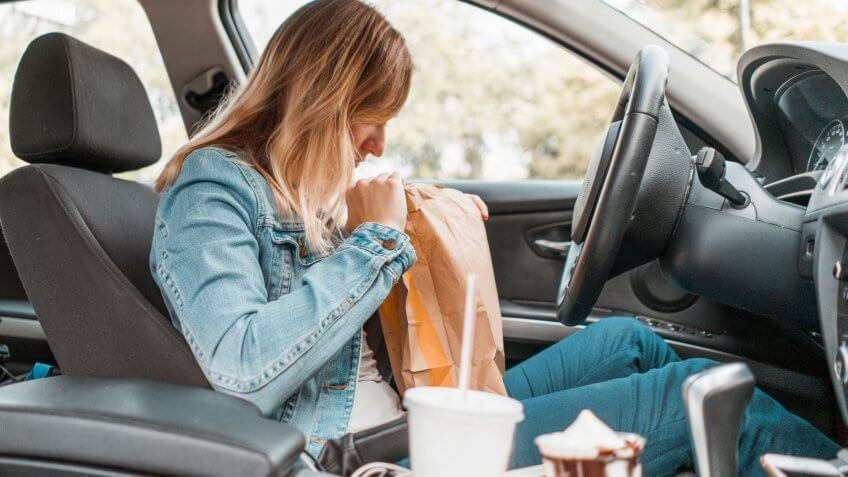 Young woman sitting in her car, opening a take out bag, eating fast food and drinking soda and coffee.