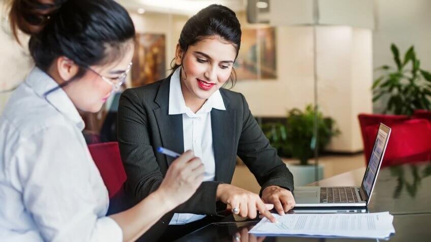 Indian female agent helping client sign the application document.