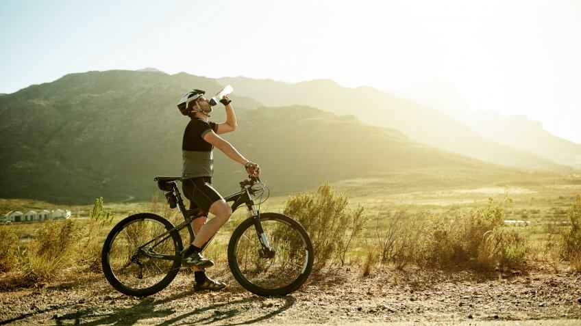 Shot of a mature man having a water break while out for a ride on his mountain bike.