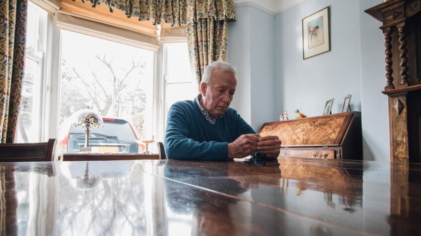 Senior man is sitting alone at the dining table in his home, with a worried expression on his face.