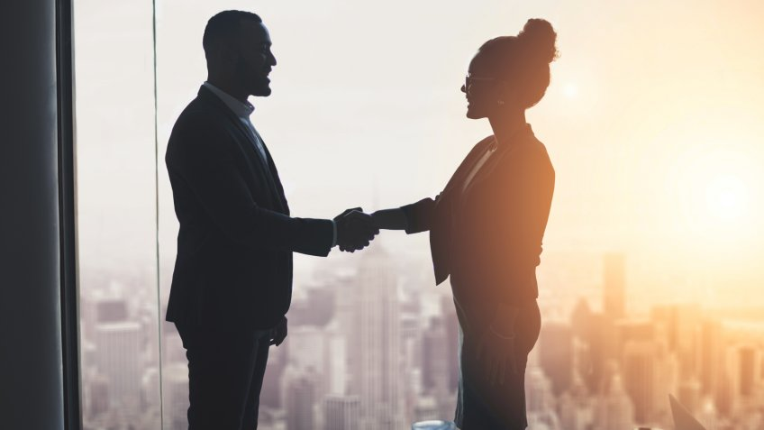 Silhouetted shot of two businesspeople shaking hands in an office.