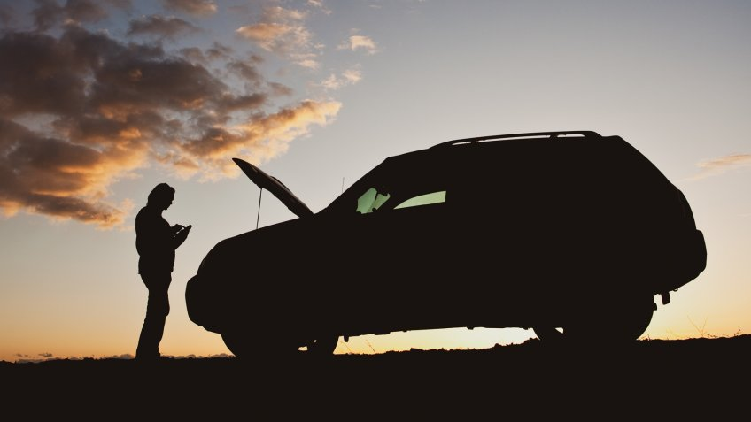 A silhouette of a woman dialing for help beside her vehicle having mechanical difficulty.