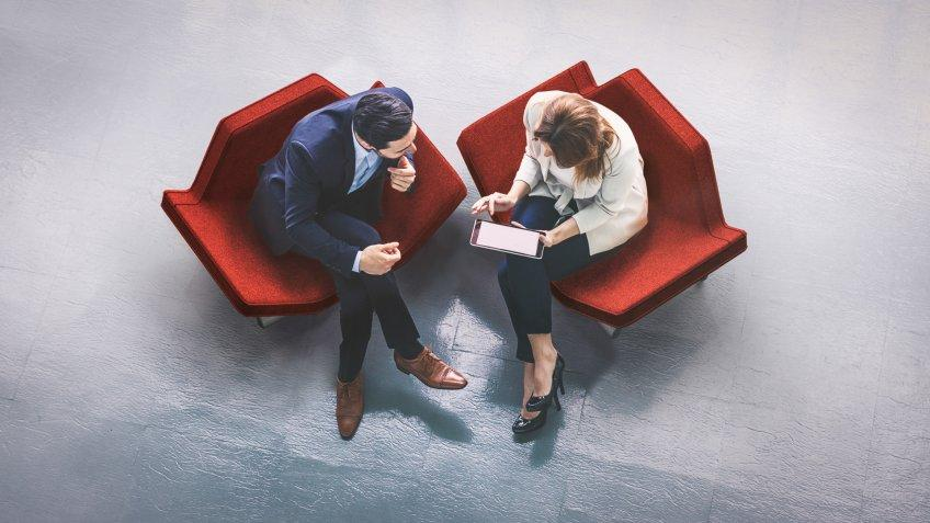 business colleagues talking in red chairs