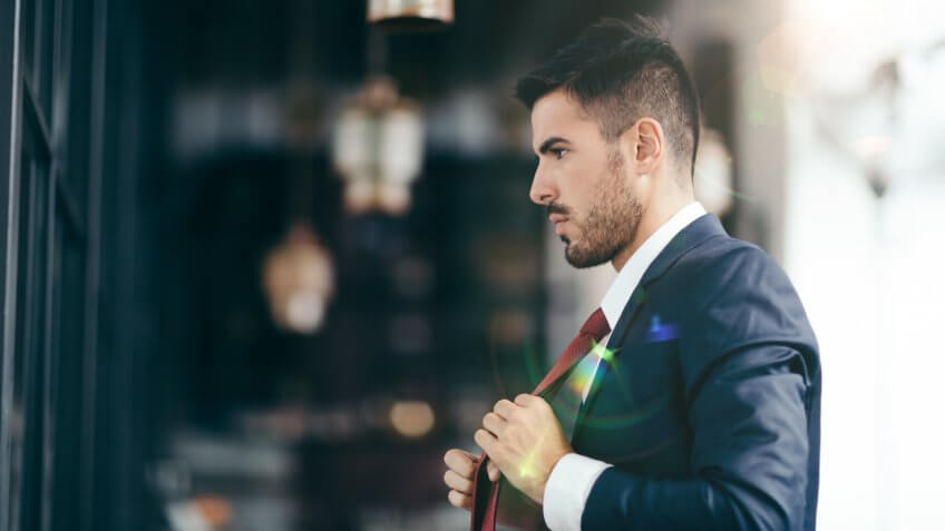 Smiling businessman fixing his necktie before going out.