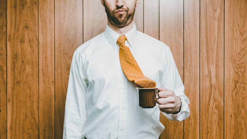 A business man in an office environment looks disappointed that his necktie has fallen in to his cup of coffee.