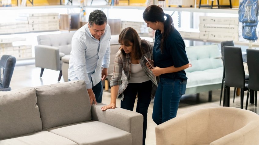 Happy couple buying a couch at a home improvement store and talking to a saleswoman - business concepts.