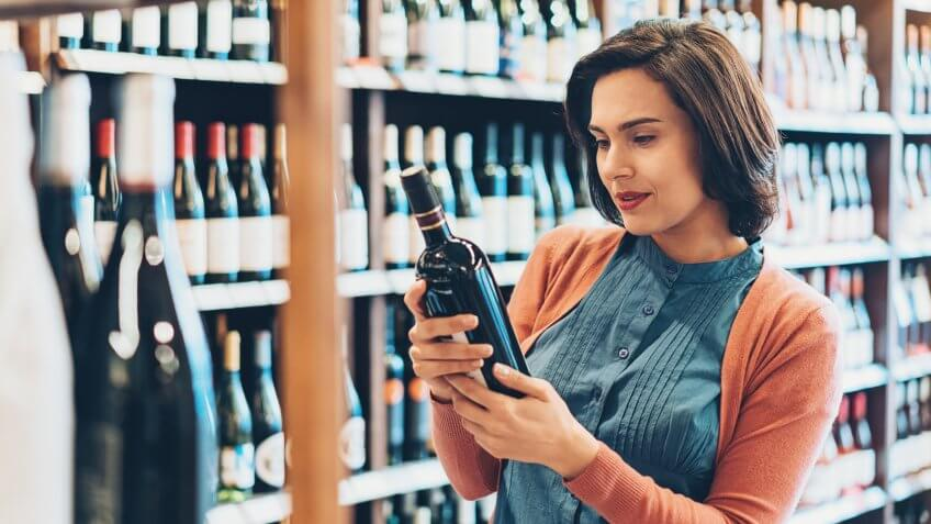 Young woman shopping for wine.