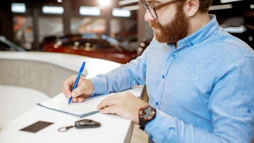 Young man signing some documents, buying or renting a car in the modern showroom of the car dealership.