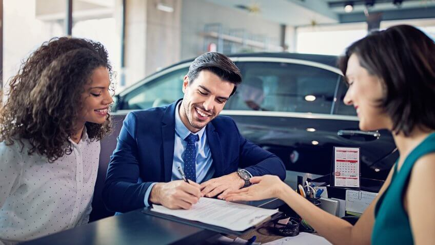 Couple is buying/lease new car and signing the contract.
