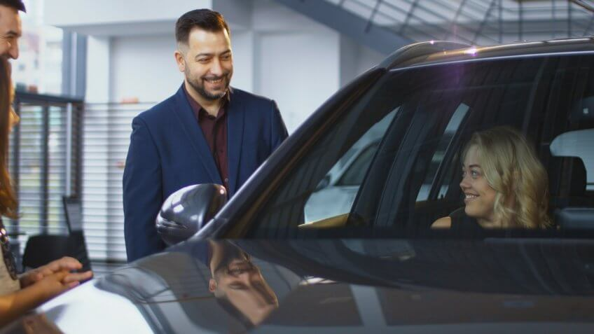 Consultant helping woman and kids to get inside of new car while testing it in dealer shop.