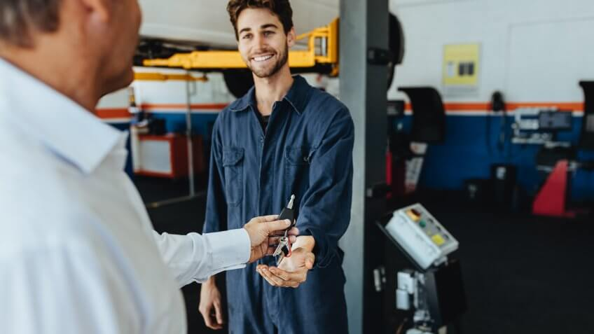 Mechanic receiving car keys from customer in automobile service center.