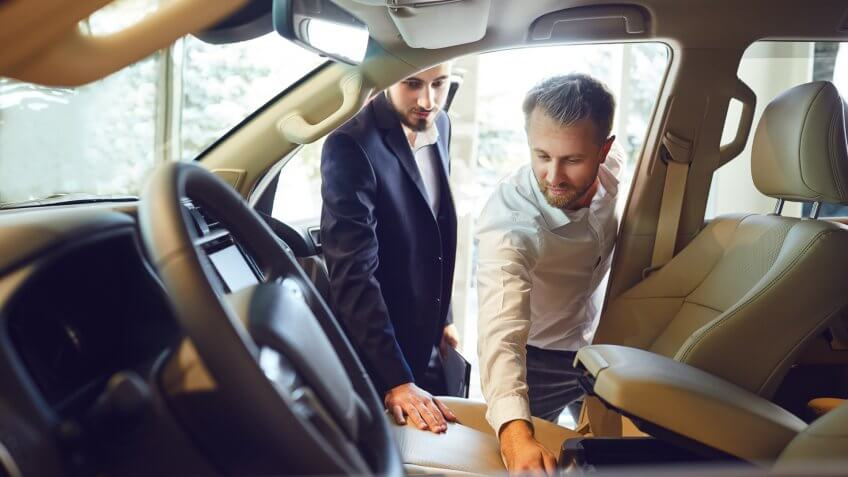 Professional salesmen selling cars at dealership to buyer.