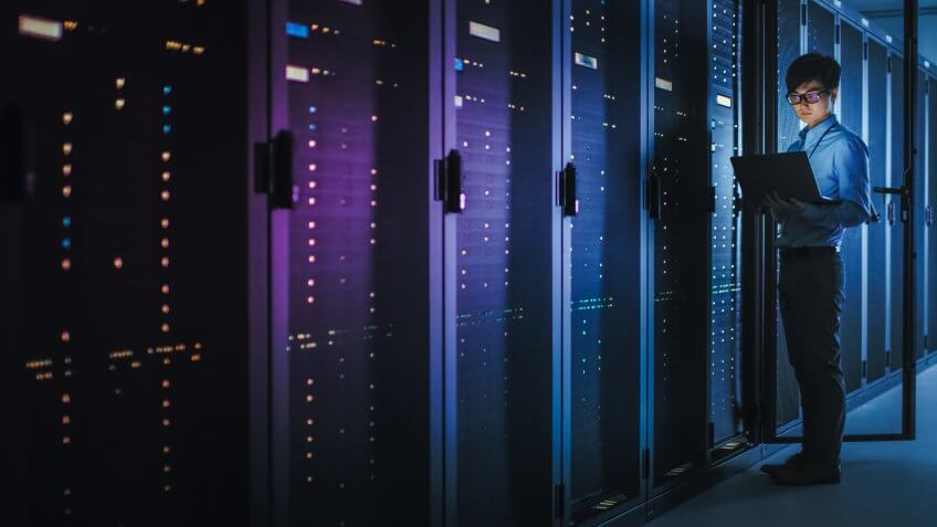 In Dark Data Center: Male IT Specialist Stands Beside the Row of Operational Server Racks, Uses Laptop for Maintenance.