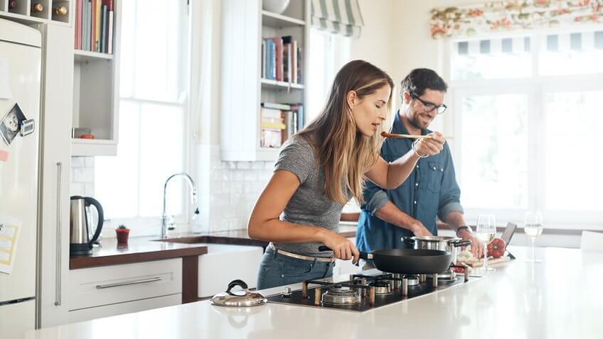Shot of a young couple cooking a meal together at home.