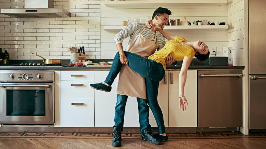 Shot of a young couple dancing in their kitchen.