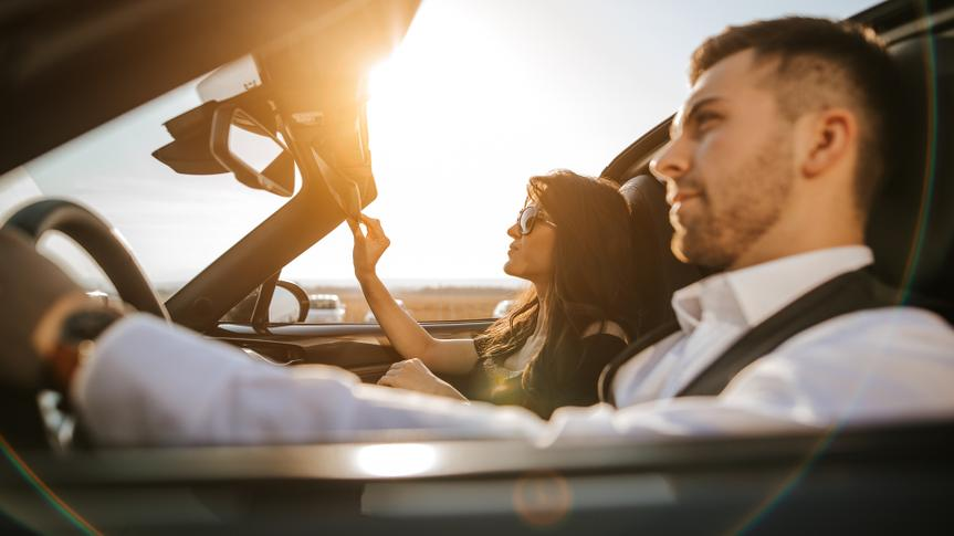 couple driving convertible new car at sunset