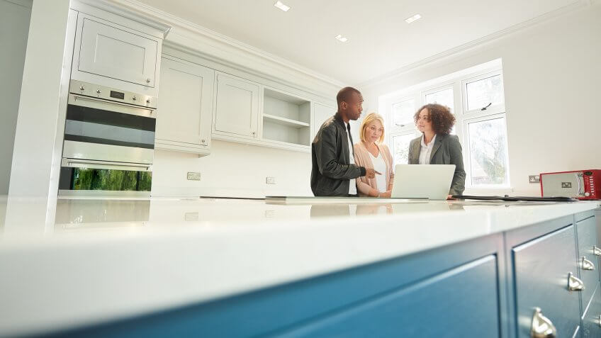 a saleswoman or estate agent shows a couple around a home with new kitchen.