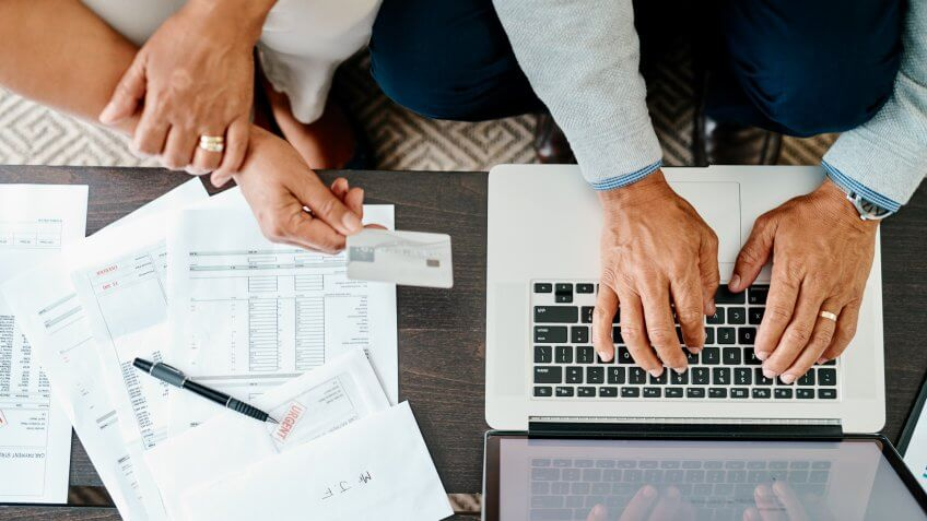 High angle shot of a couple using a laptop and credit card while sorting their finances together at home.