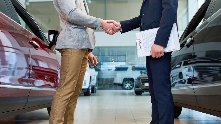 Low section side view of  handsome client shaking hands with sales manager in car showroom, after buying brand new luxury car.