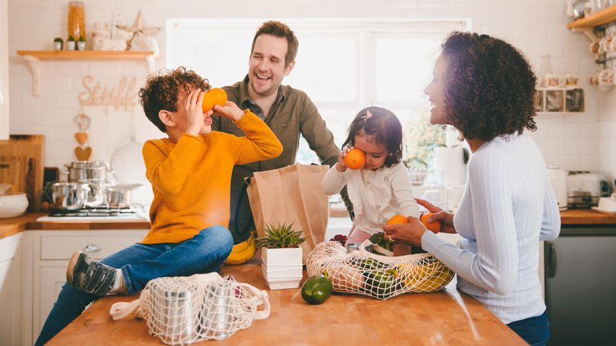 Family Returning Home From Shopping Trip Using Plastic Free Bags Unpacking Groceries In Kitchen.