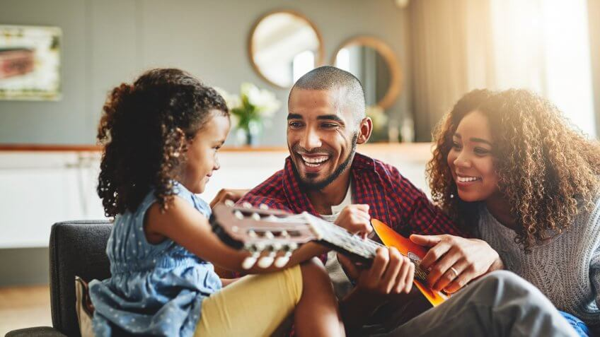Shot of an adorable little girl and her parents playing a guitar together on the sofa at home.