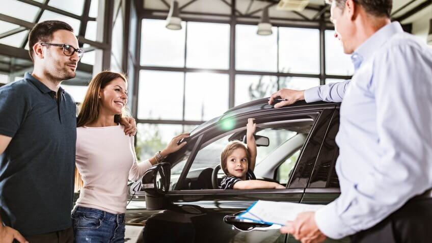 Young happy parents communicating with salesperson while buying a car in a showroom.