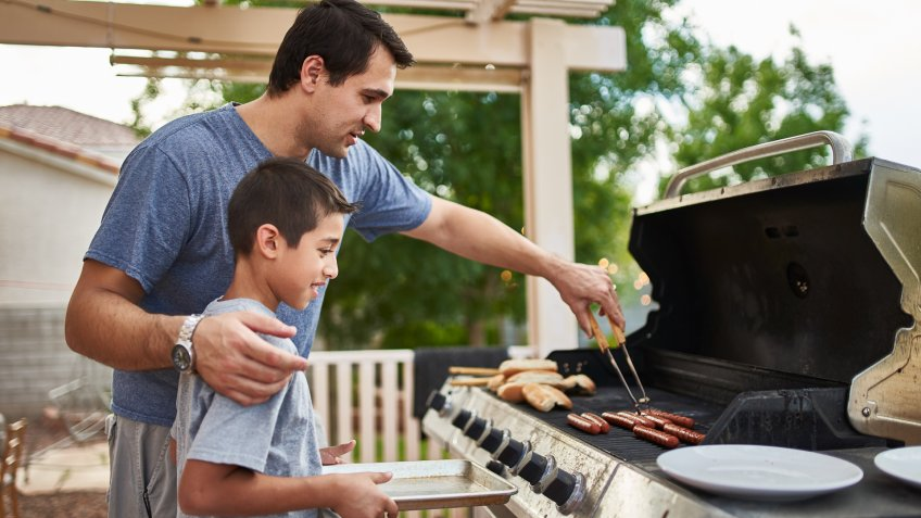 father teaching son how to grill hot dogs and bonding during the day.