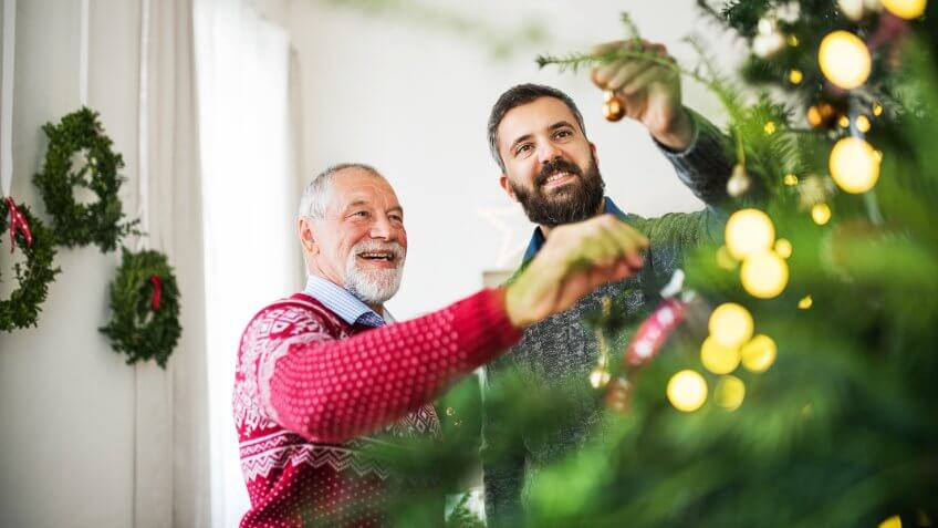 A happy senior father and adult son decorating a Christmas tree at home.