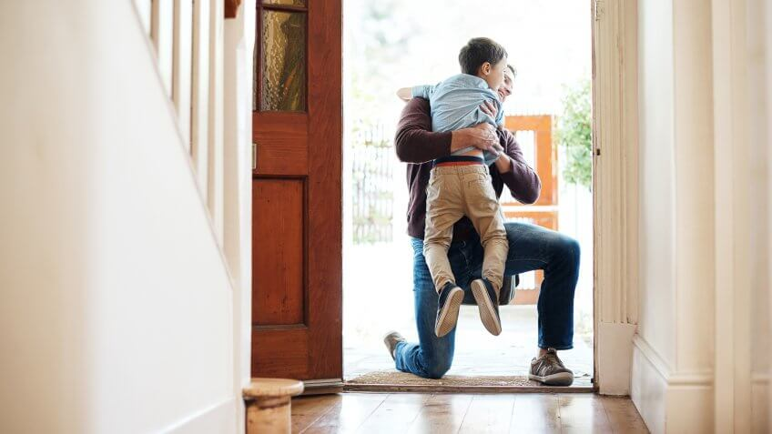 Shot of a little boy running into his father's arms as he arrives at home.