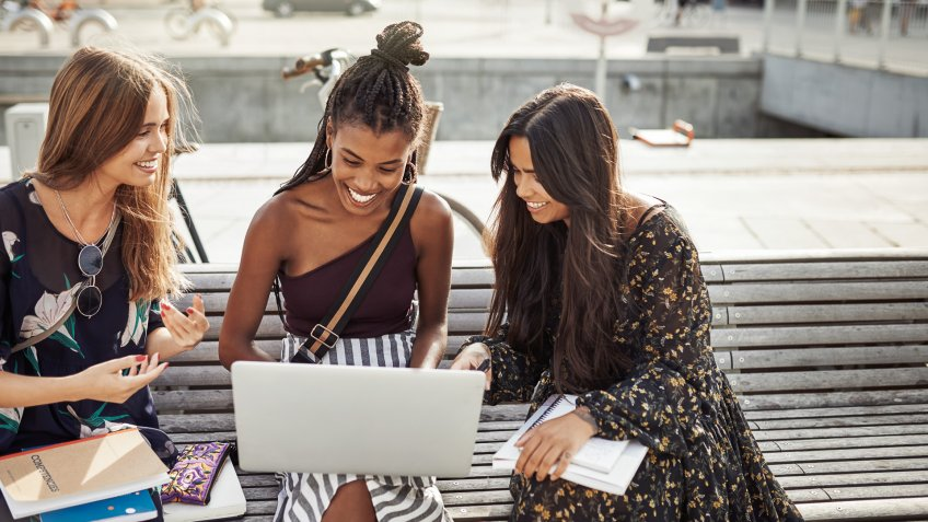 Shot of young women studying together outdoors.