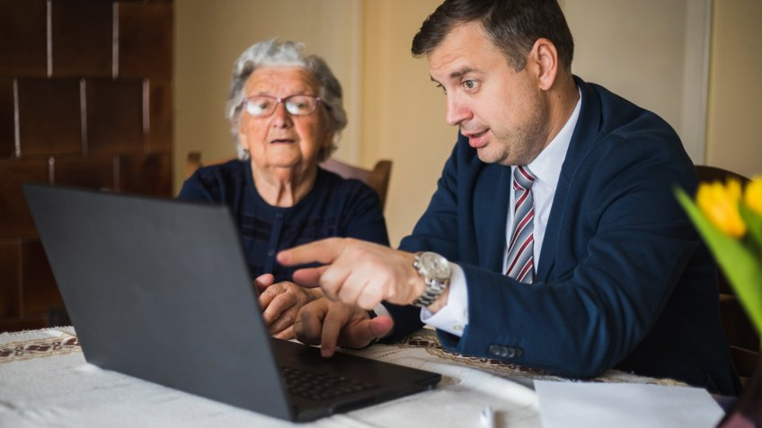 Man in business suit showing something on laptop to old lady.