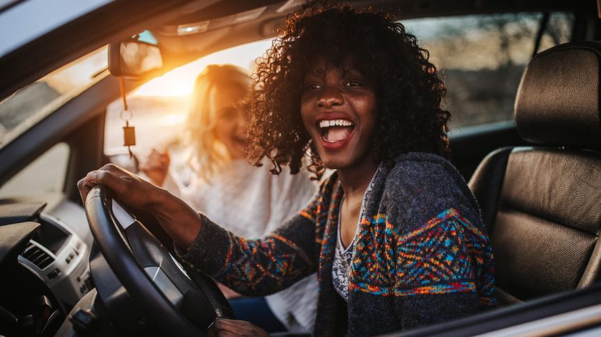 Happy female friends on road trip.