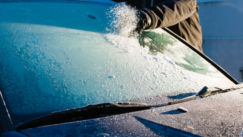 A man cleans frozen windshield by scratching, cold morning.