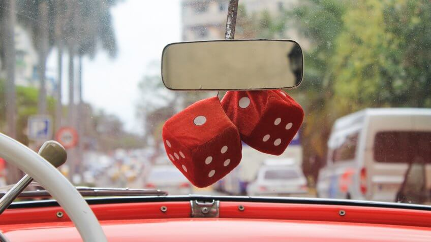 Fuzzy red dice on a vintage red car in Havana.