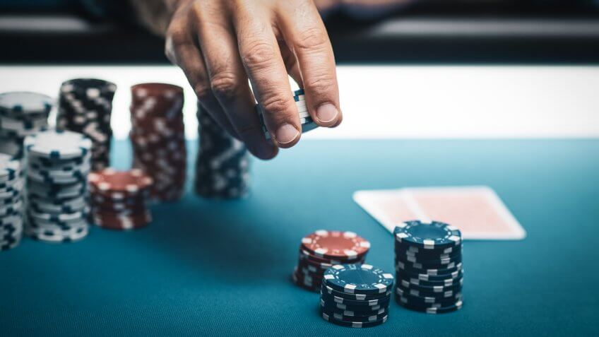 Successful player betting chips at casino and Hold 'em poker cards on the table, games and gambling concept.