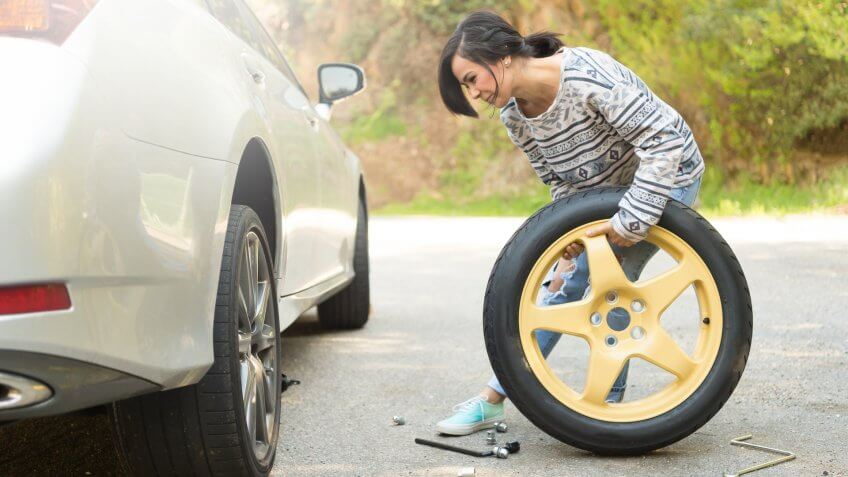 A young hispanic women stranded on the side of the road changing a flat tire.