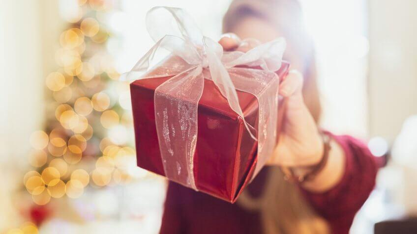 Unrecognizable woman holds a Christmas present wrapped in red paper and tied with a white transparent bow.