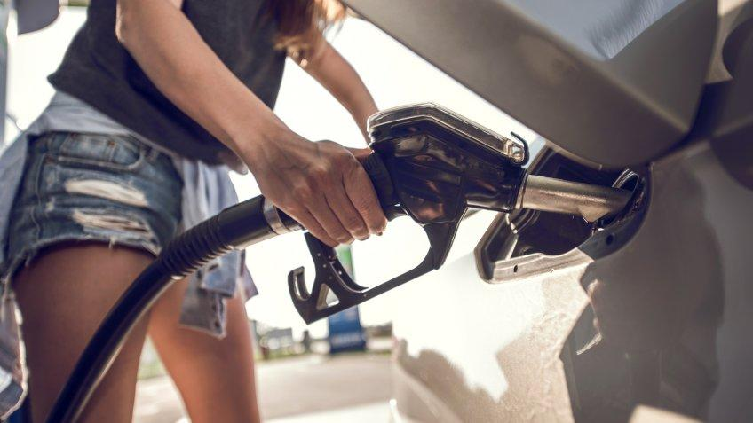 Unrecognizable woman filling a gas tank of her car at gas station.