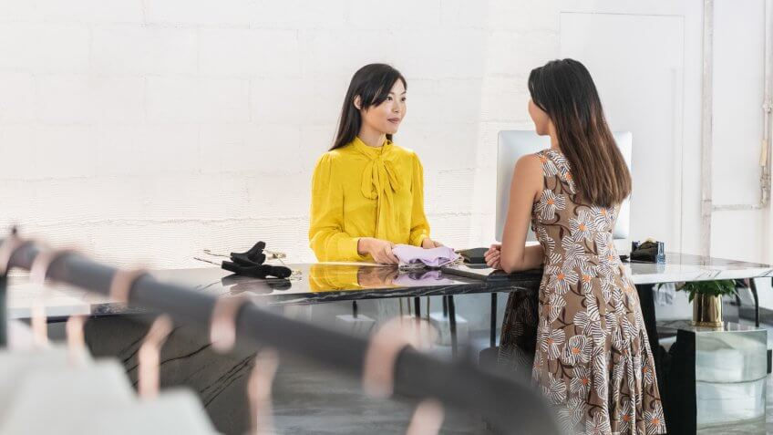 Young woman in floral dress standing at counter and discussing with shop worker, buying clothed, service, consumer rights, decisions.