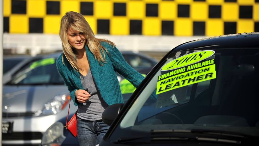 A young woman shopping for cars.