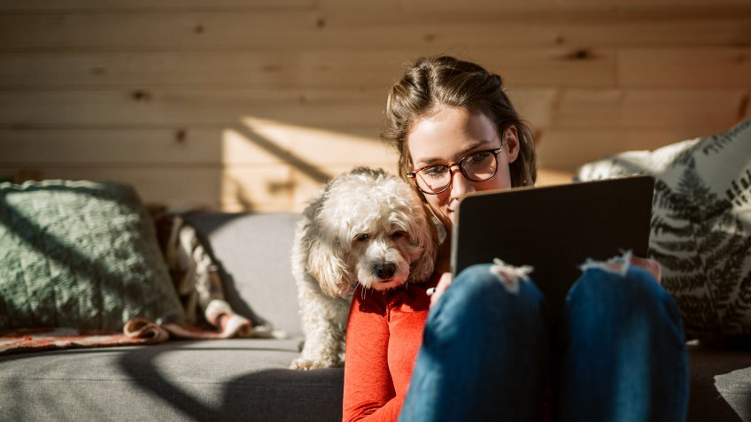Female Artist Drawing At Home In Company Of Her Cute Poodle Dog.
