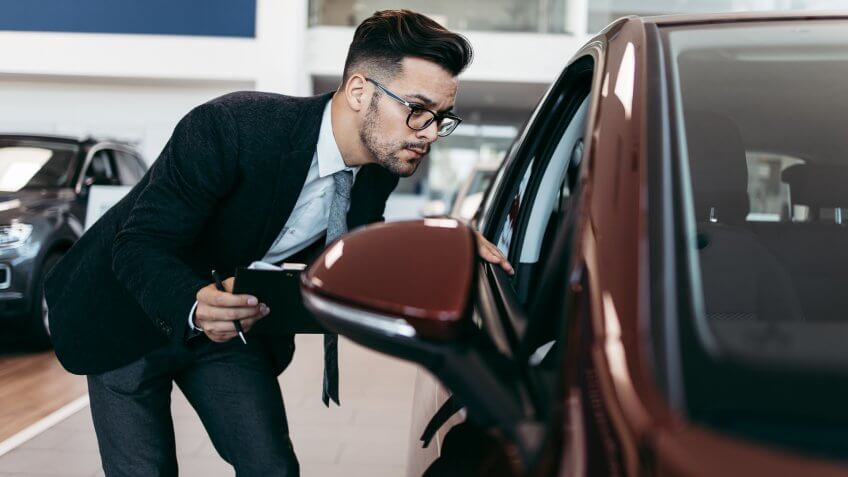 Car seller working in showroom and quality control checking of car details for the last time before buyer comes.