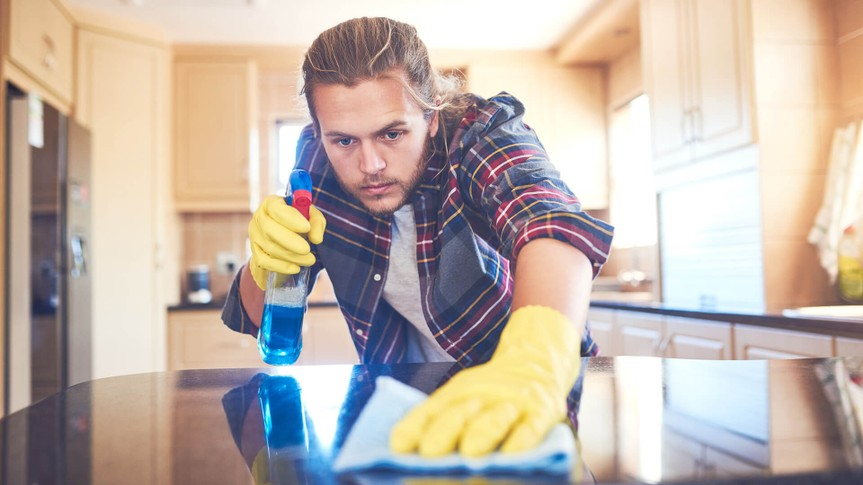 Shot of a young man cleaning his home.