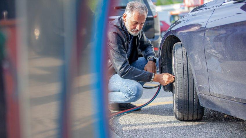 Mature Man Inflating Car Tires.