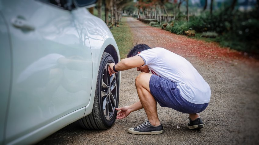 Young asian man checking car air tire while travel at Countryside.
