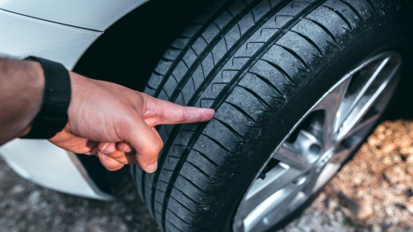 A human hand checking a tire tread.