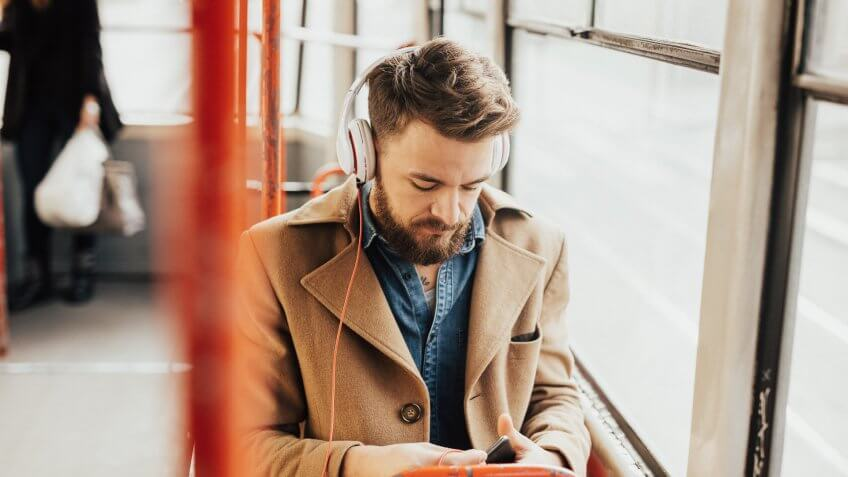 Handsome guy listening to the music on public transport.