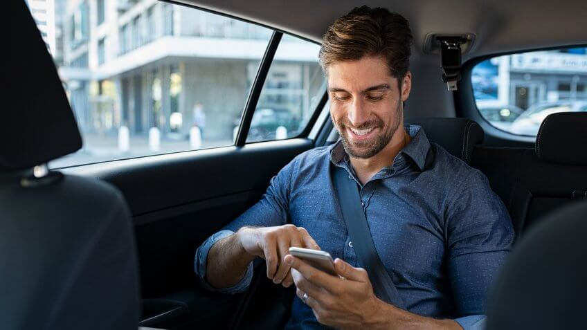 Happy smiling businessman man typing message on phone while sitting in a taxi.