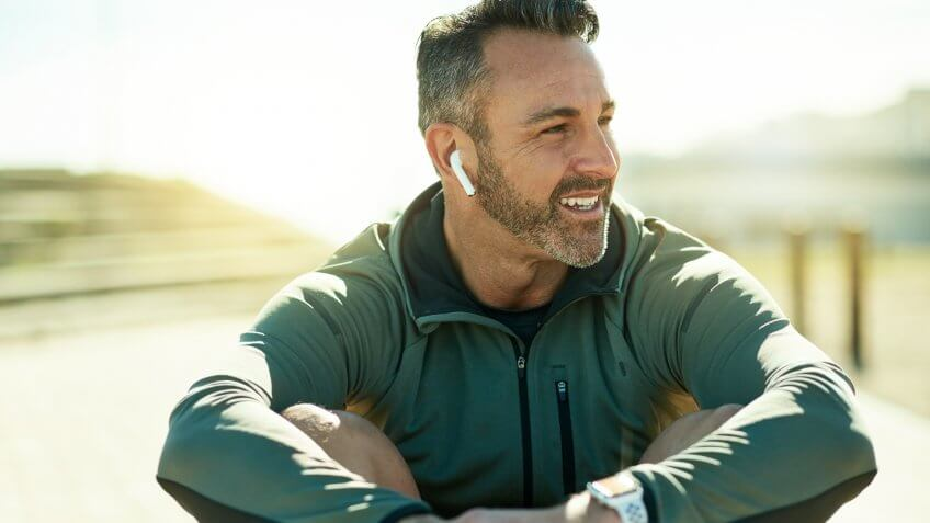 Shot of a mature man using wireless earphones while out for his workout.